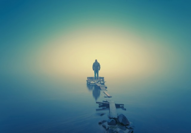 Lonely-man-standing-on-the-wooden-jetty-in-the-autumn-foggy-river-with-stones-gangway-805x563